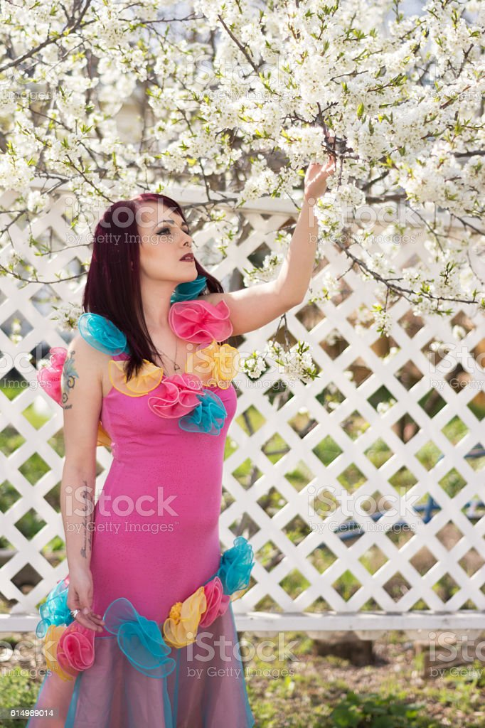 Vertical image of young woman in Spring garden looking up. stock photo