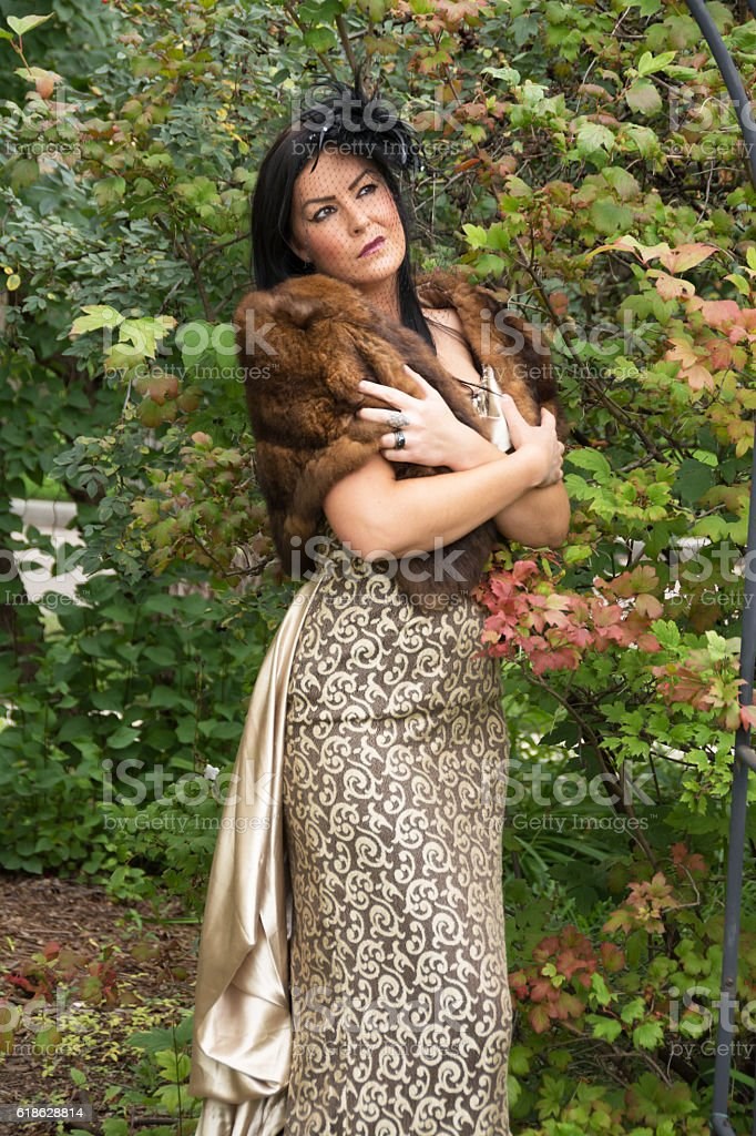 Vertical of woman in fur stole and long dress outdoors. stock photo