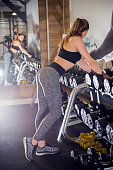 Vertical photo of Gym woman Choosing Weight