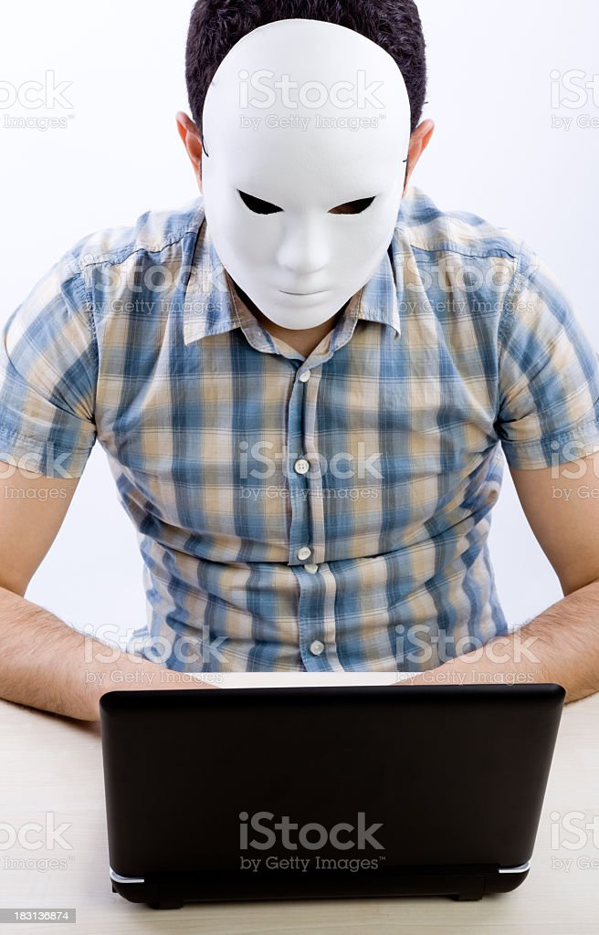 Vertical Photo Of Man With Mask Using Computer For Hacking stock photo