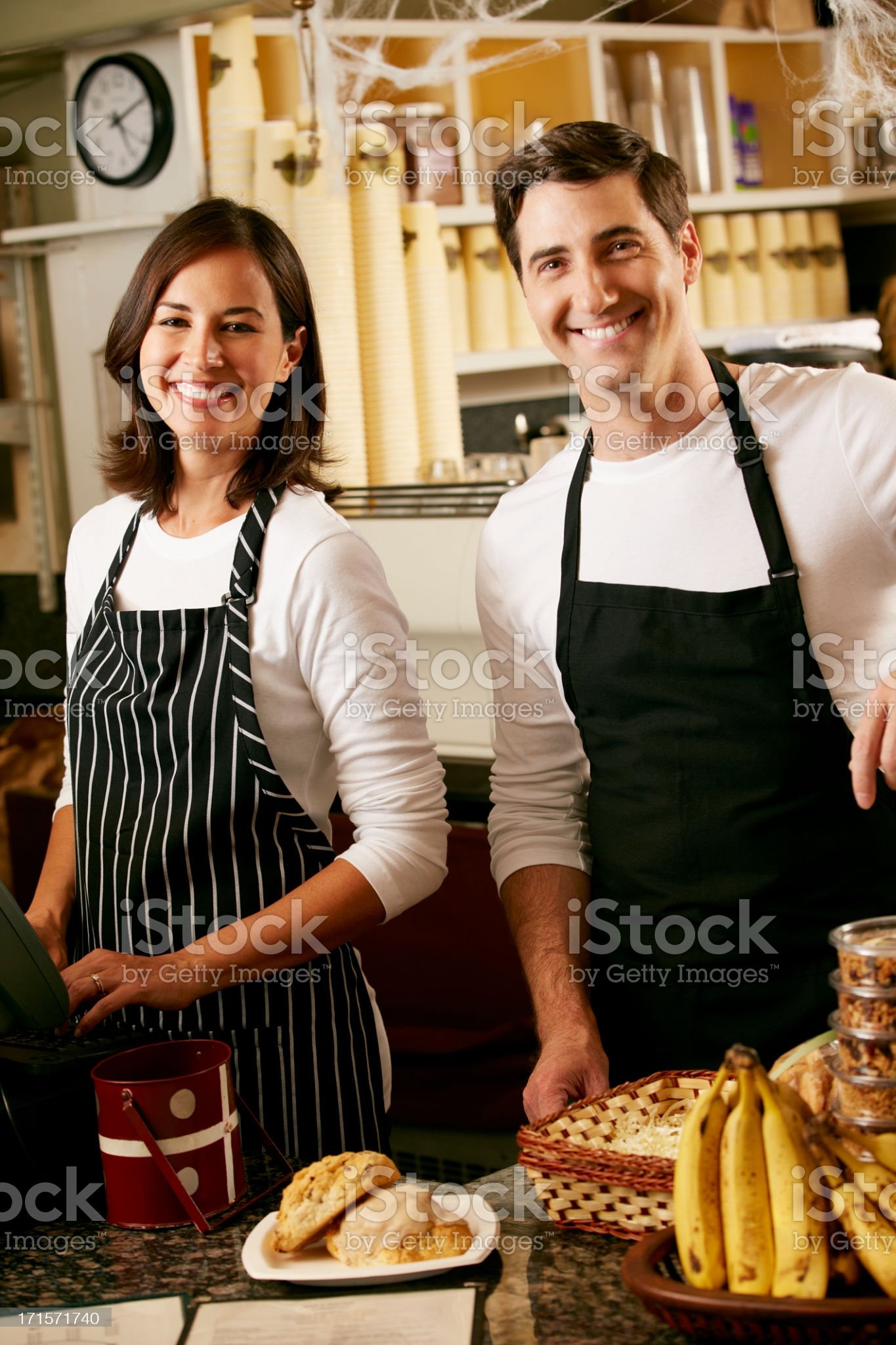 Vertical portrait of couple wearing aprons in coffee shop royalty-free stock photo