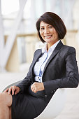 Vertical portrait of smiling Asian businesswoman, sitting