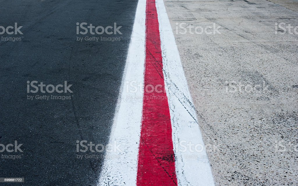 Vertical red and white lines on dark grey asphalt stock photo
