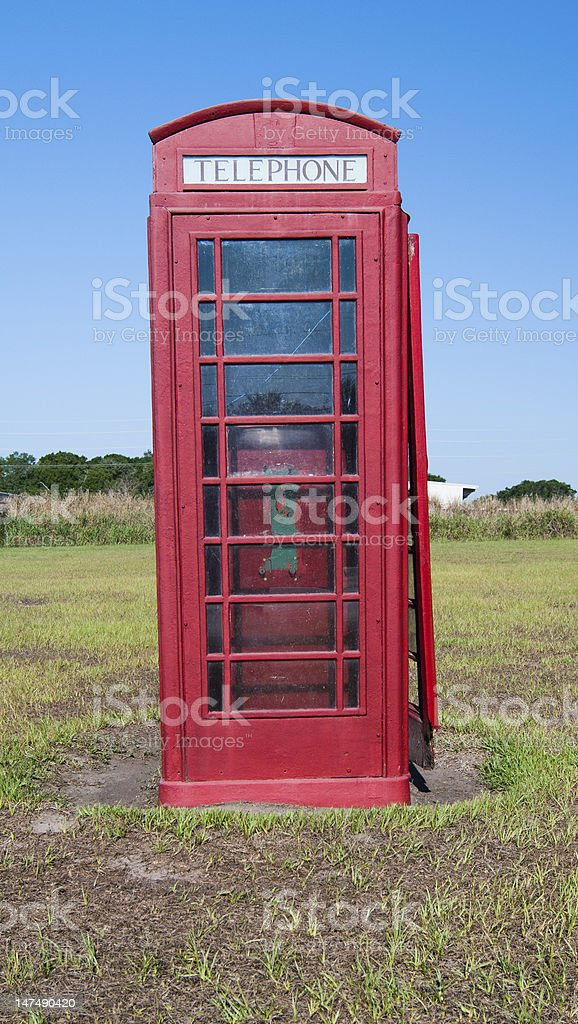 Vertical Red Traditional English Telephone Booth in Field royalty-free stock photo