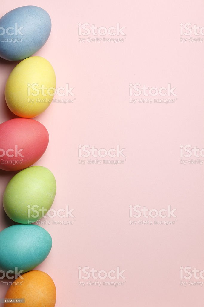 Vertical row of Easter eggs on pink background stock photo