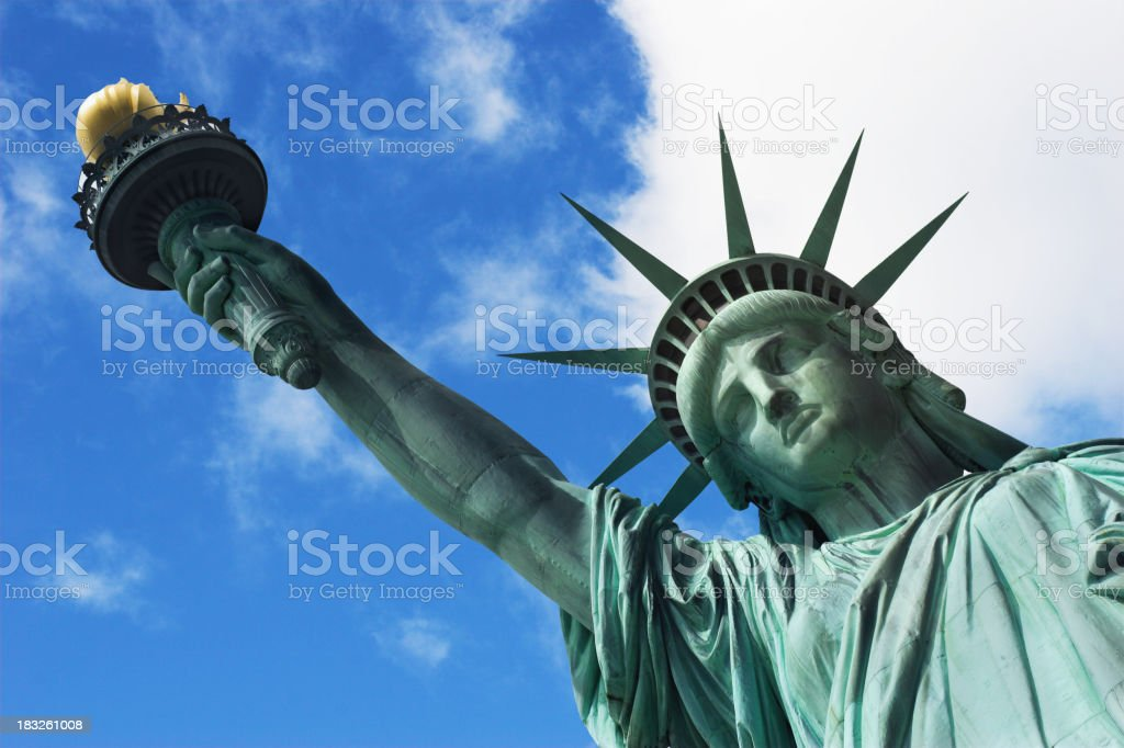 Vertical shot looking up at Statue of Liberty on sunny day stock photo