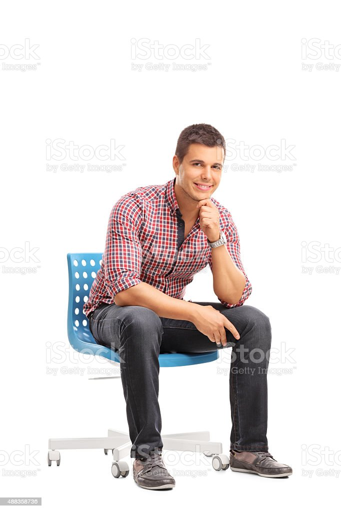 Vertical Shot Of A Casual Guy Sitting On A Chair Stock Photo
