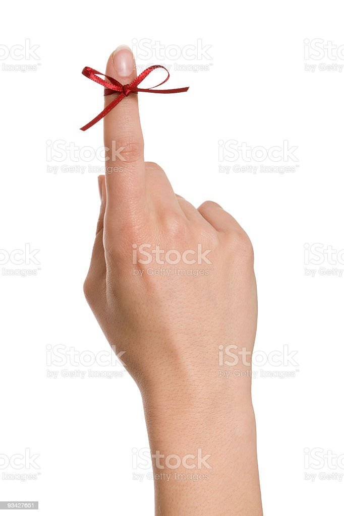 Vertical shot of a hand with a red string tied to finger royalty-free stock photo