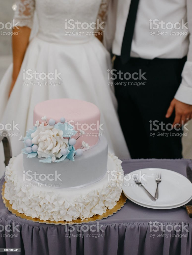 Vertical shot of a pastel colored wedding cake with bride and groom at the background stock photo