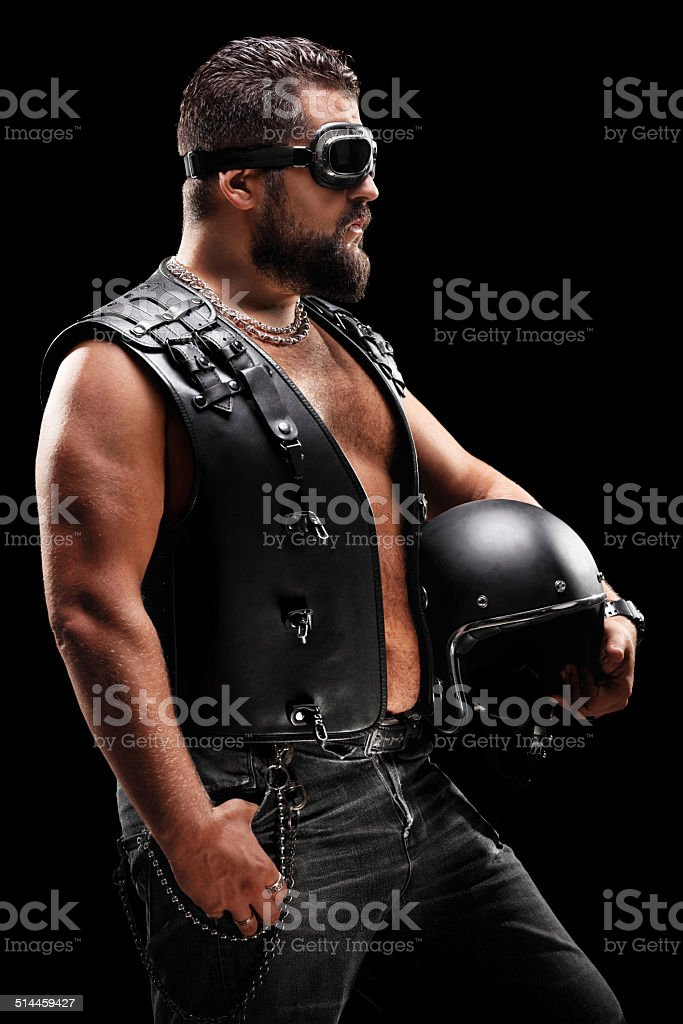 Vertical shot of male biker holding a helmet stock photo