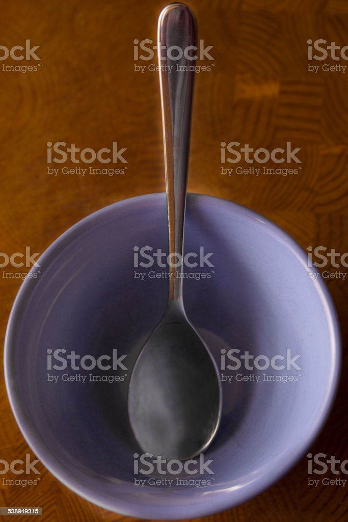 Vertical Spoon Centered inside a blue cereal Bowl stock photo