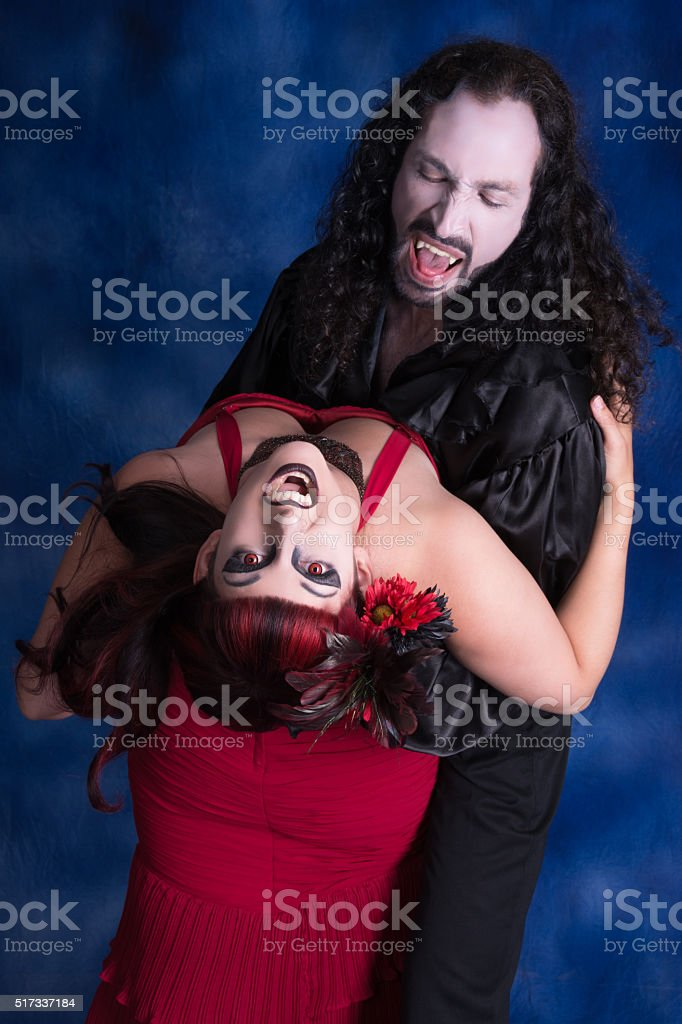 Vertical three quarter colour image of two vampires dancing. stock photo