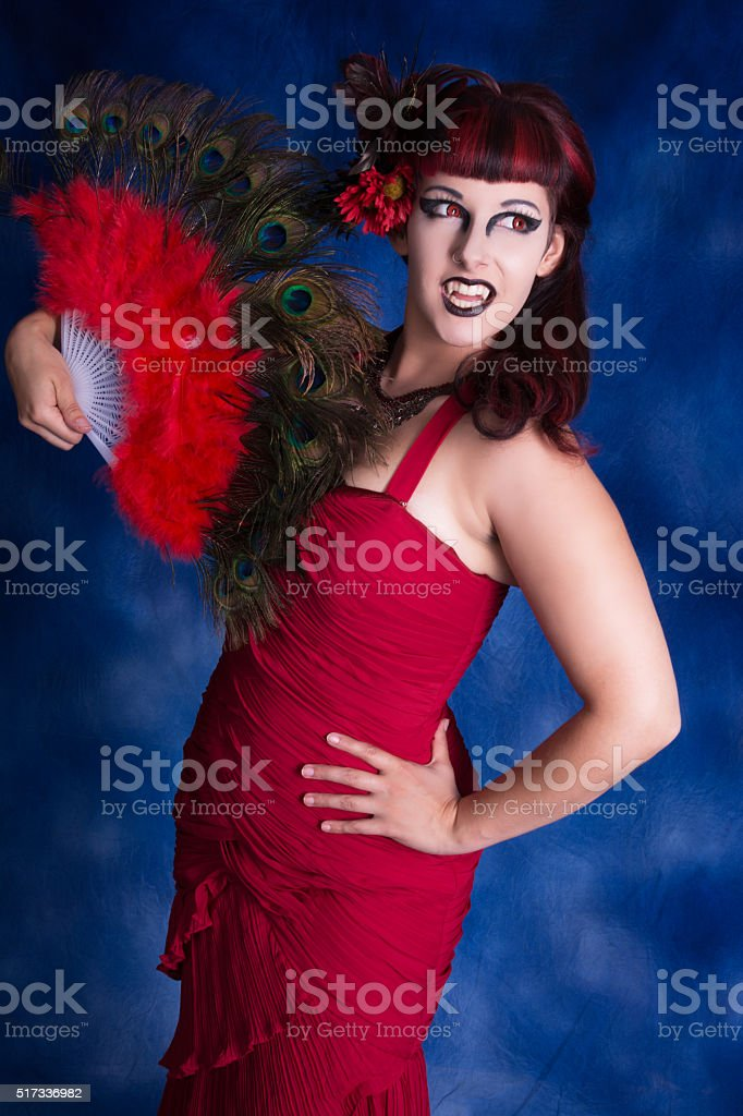 Vertical three quarter colour portrait of female vampire with fan. stock photo