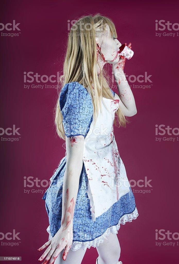 Vertical three quarter length of Zombie Alice drinking. stock photo