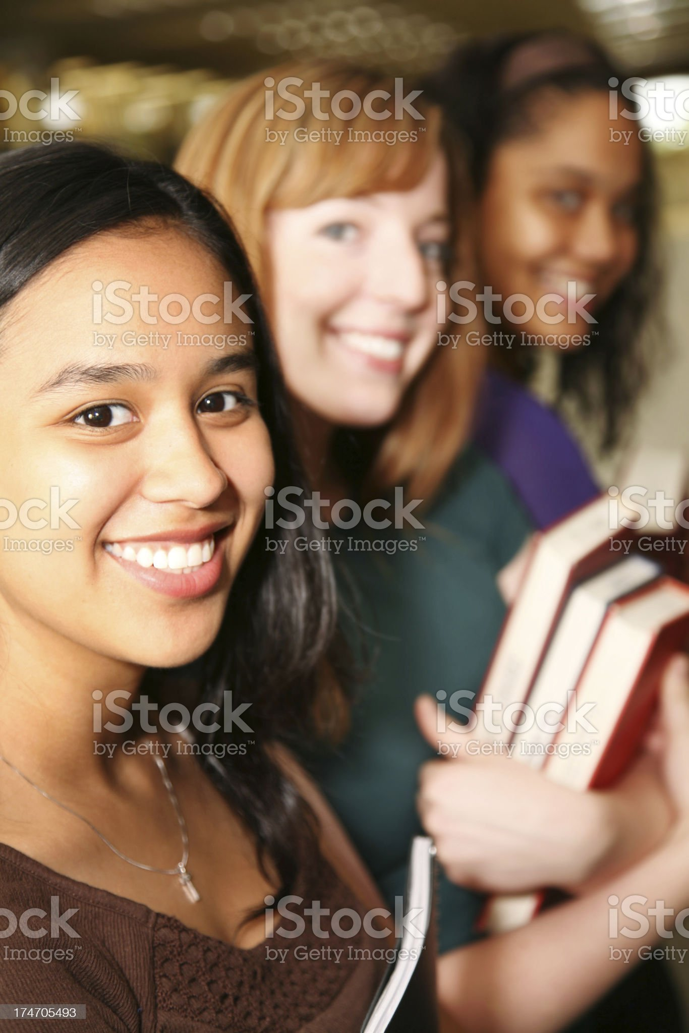 Vertical View of Three Female College Students in the Library royalty-free stock photo