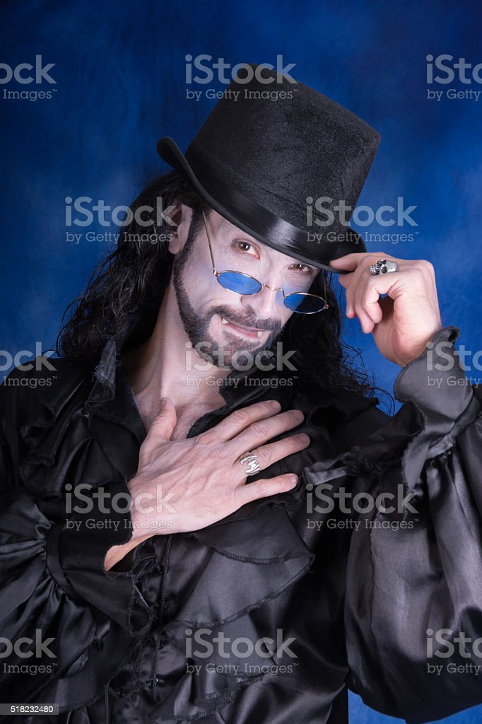 Vertical waist up colour portrait of male vampire, touching chest. stock photo