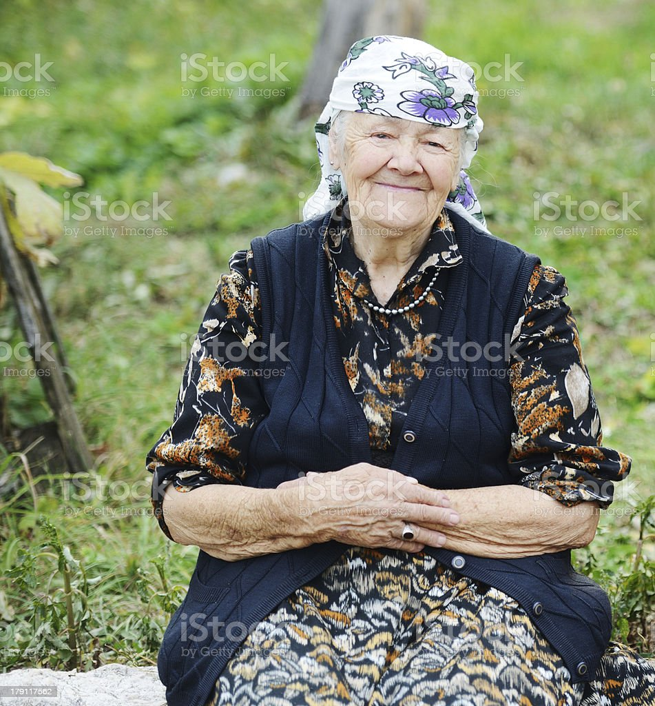 Very aged woman sitting in nature, portrait stock photo