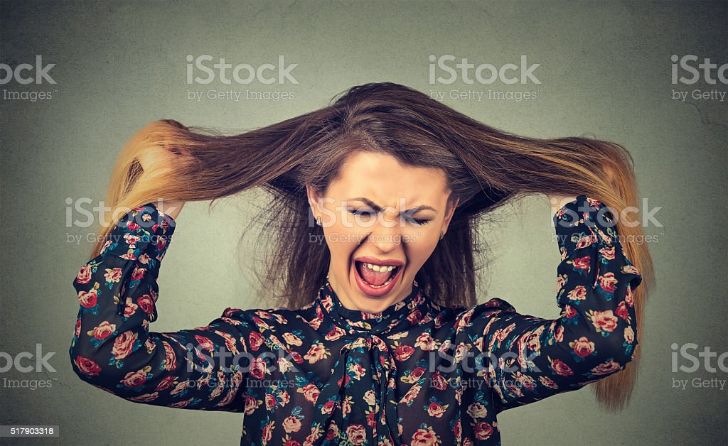 Very angry woman pulling her hair out screaming stock photo