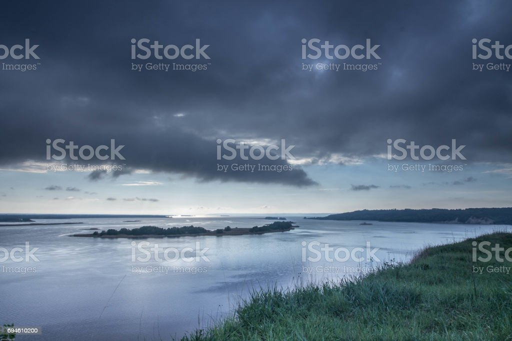 Very cloudy weather. Black clouds over the river. The edge of the river bank. stock photo