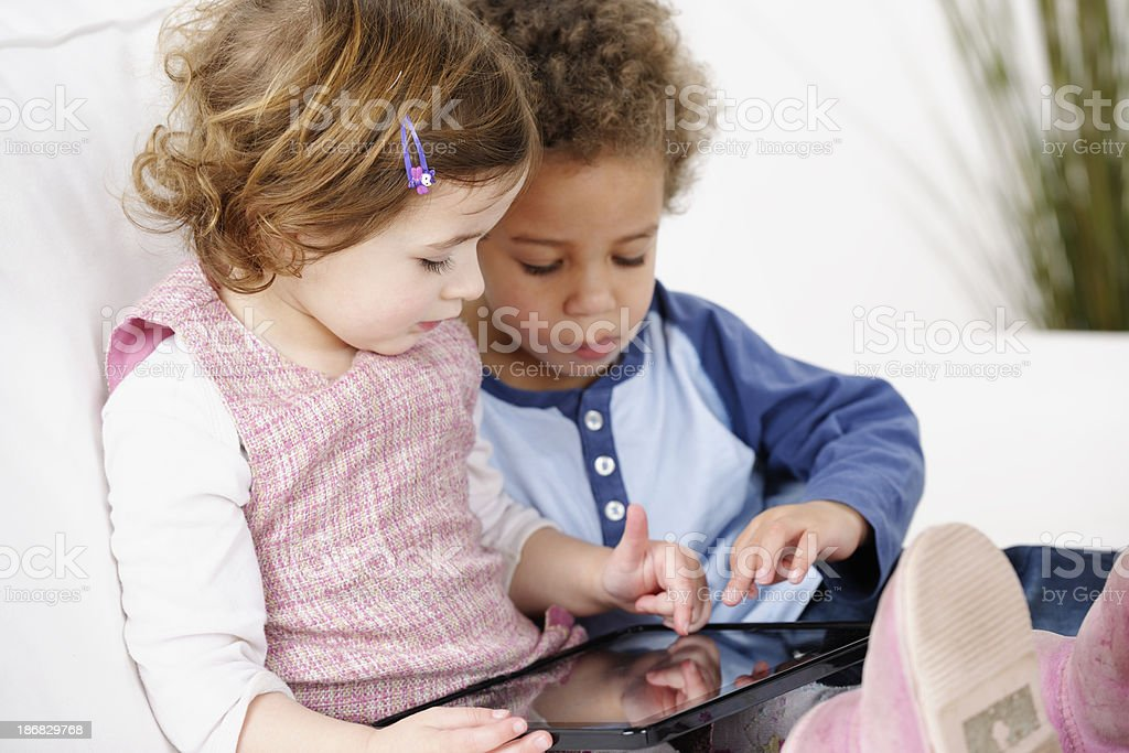 Very Cute Pair Of Toddlers Using Digital Tablet royalty-free stock photo