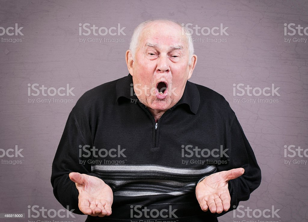 Very emotional old man gesticulates hands on a gray background. stock photo