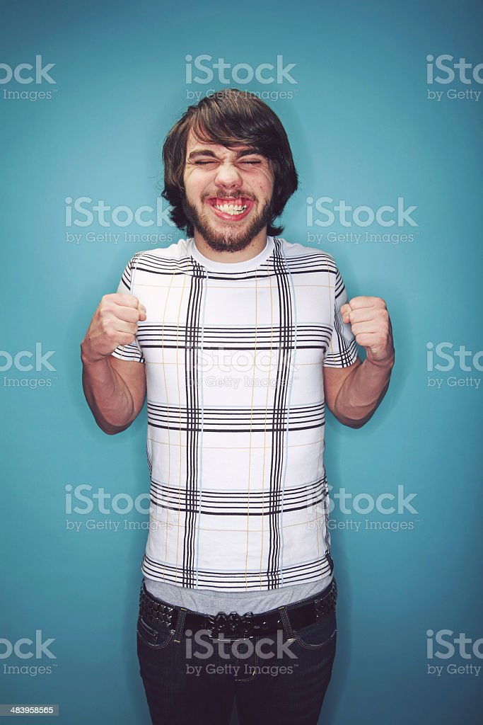 Very Excited Young Man Against Blue Wall royalty-free stock photo
