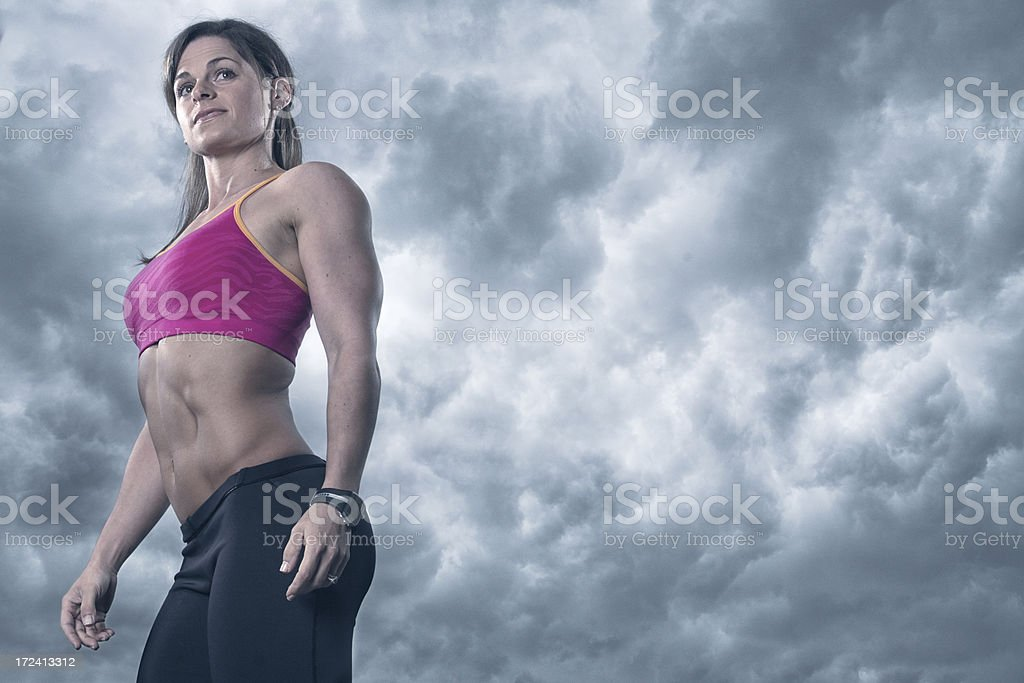 Very Fit Woman looking away on Cloudy Background royalty-free stock photo