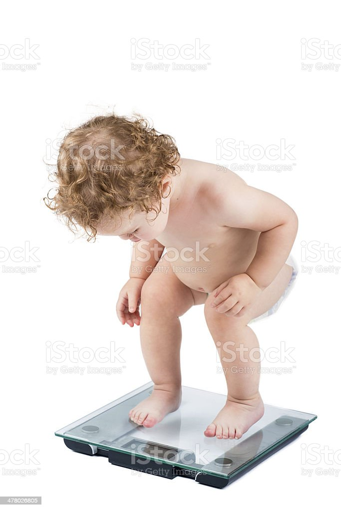 Very funny baby watching her weight, isolated on white stock photo