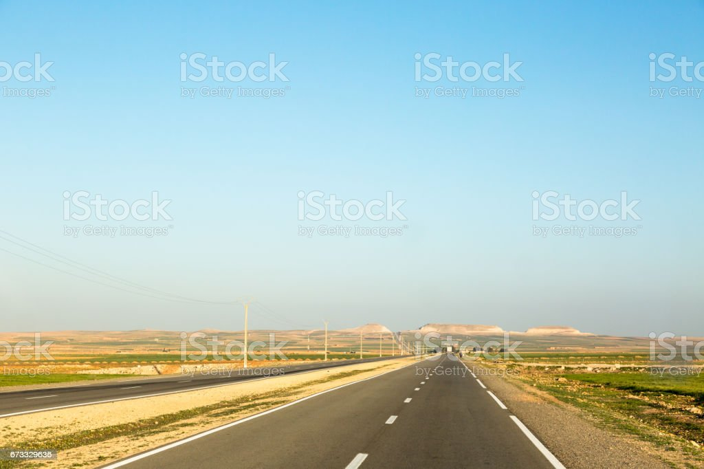 Very long straight empty highway in Morocco with low horizon and blue clear sky stock photo