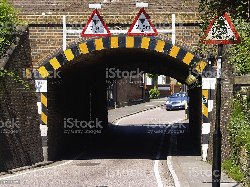 Very low, narrow railway bridge with multiple warning symbols royalty-free stock photo