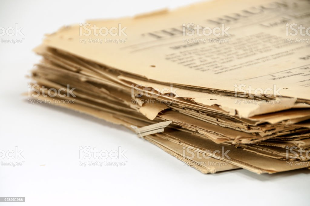 Very old, 110 years, newspaper stack on white  copy space stock photo