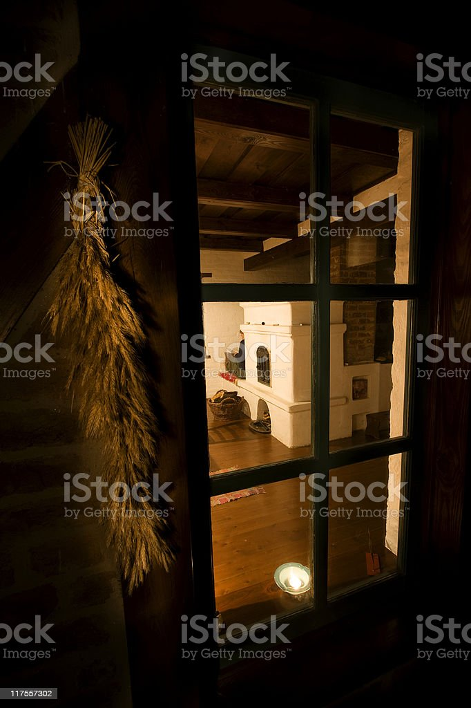 Very old fireplace through a window with wheat-sheaf and tea-light royalty-free stock photo