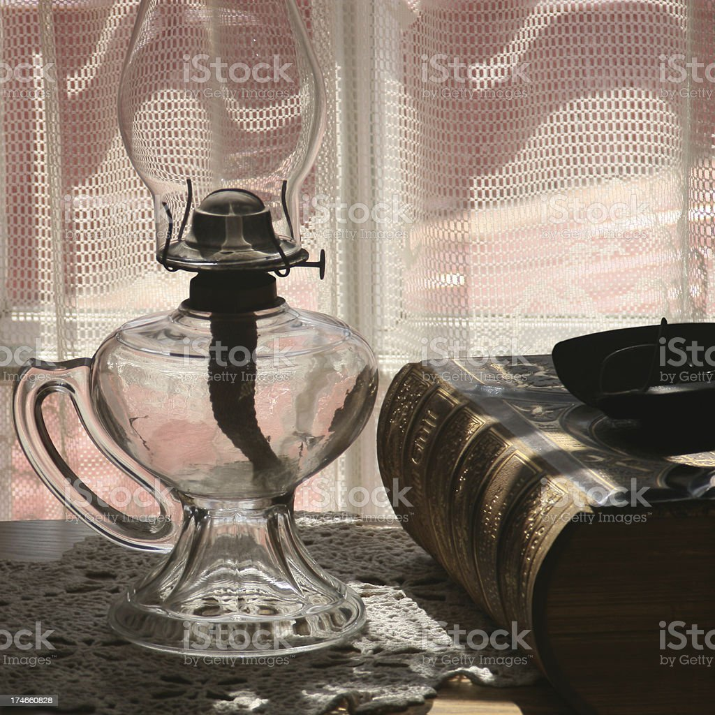 Very old hurricane lamp, book and glasses. stock photo