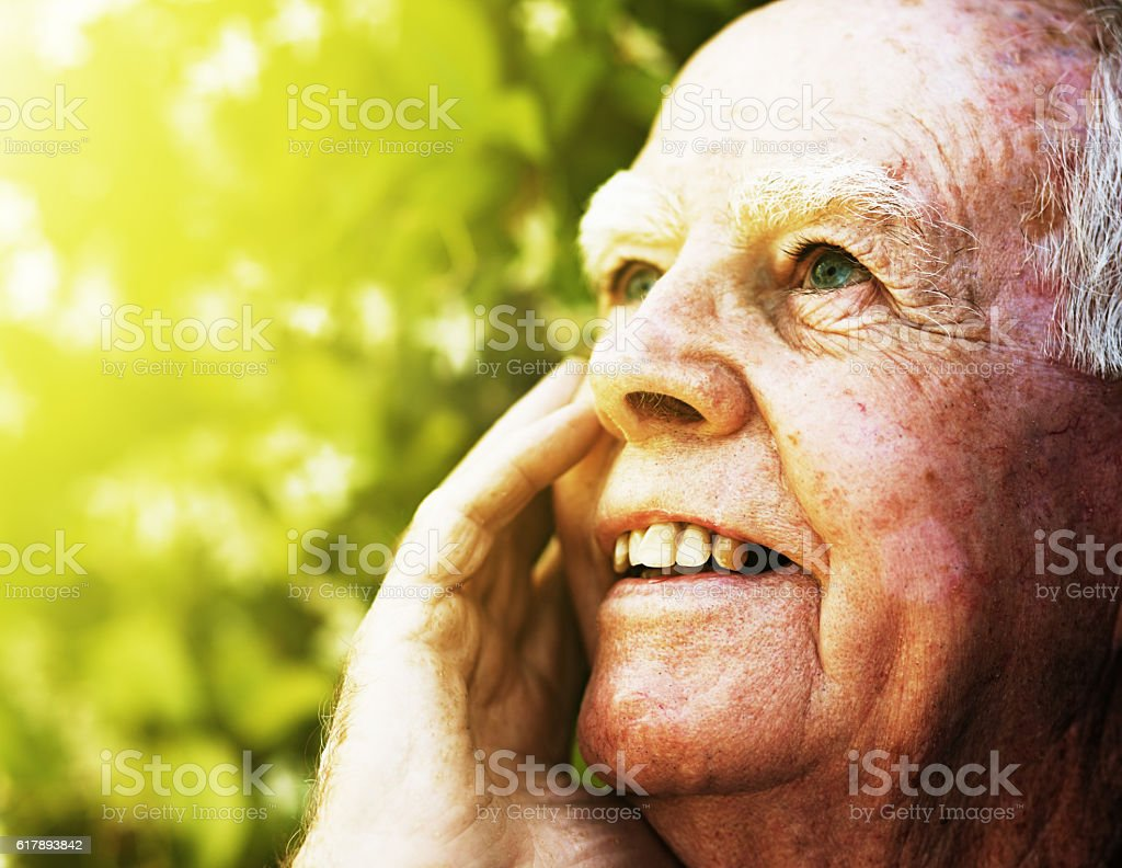 Very old man in garden looks up, smiling, hand raised stock photo