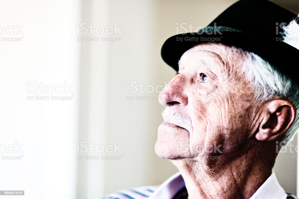 Very old man in Tyrolean hat looking serious in profile stock photo