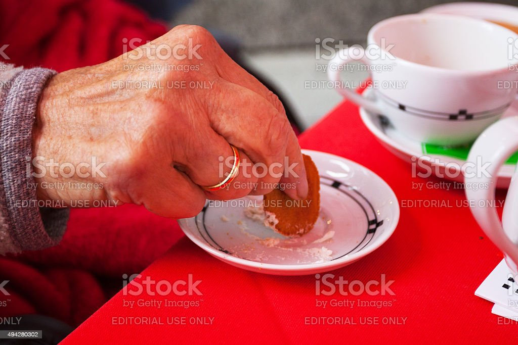 Very old senior woman is taking cake with creme stock photo