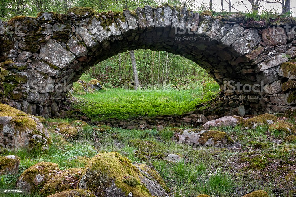 Very old stone bridge over a dried out river stock photo