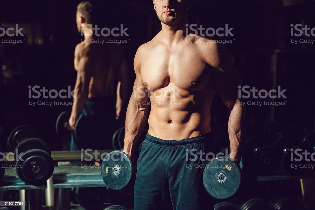 Very power athletic guy bodybuilder , execute exercise with dumbbells stock photo