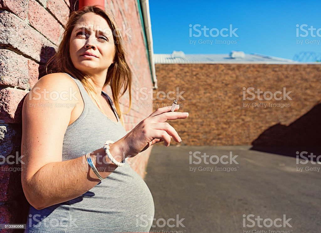 Very pregnant woman sneaks a guilty cigarette stock photo