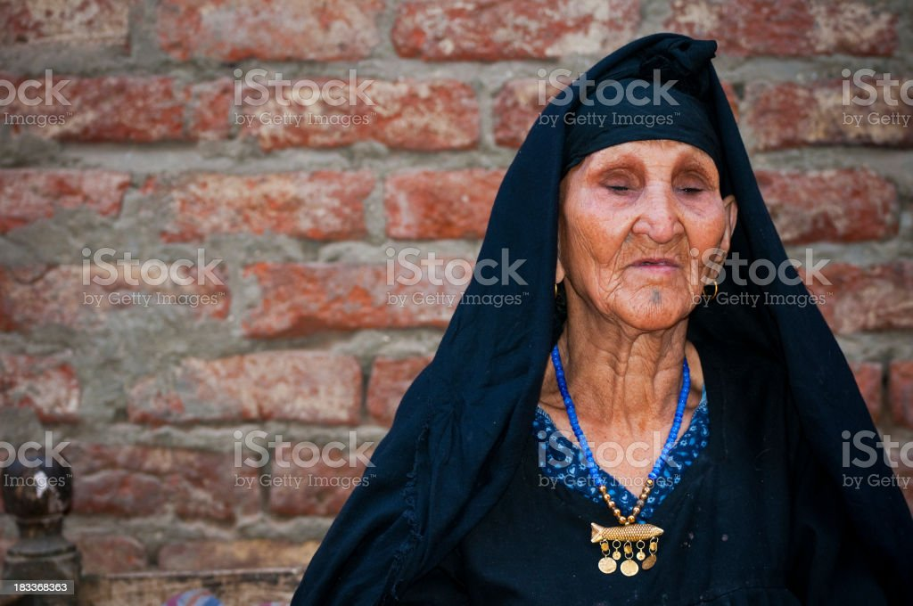 Very senior Arab woman outside home in Luxor, Egypt royalty-free stock photo