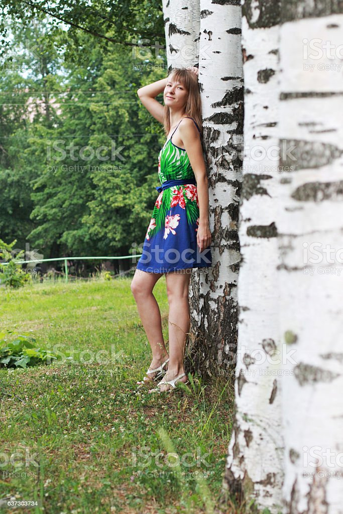 very slender girl leaned against a birch tree stock photo
