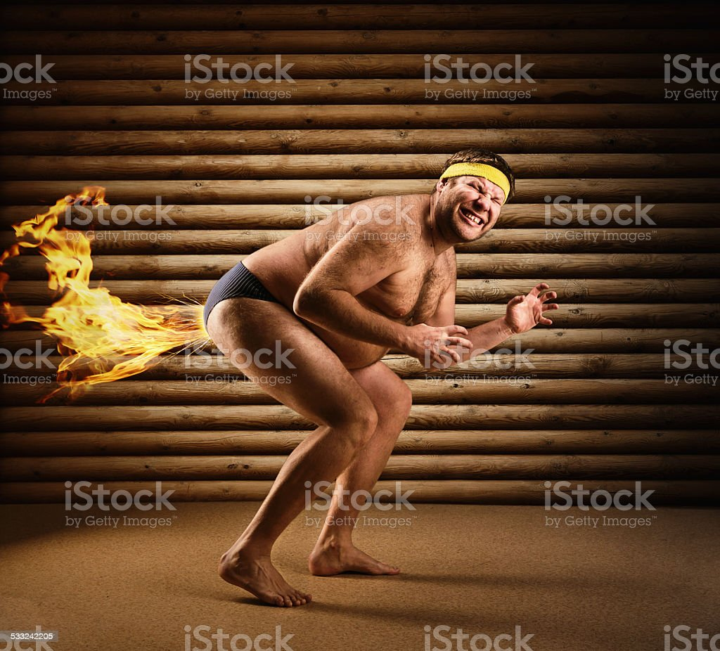 Very strange naked man farts by fire stock photo