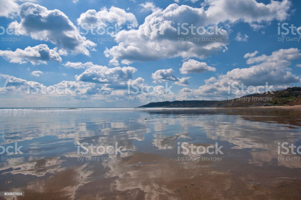 A very strong reflection of the sky across the beach at Charmouth in Dorset, England stock photo