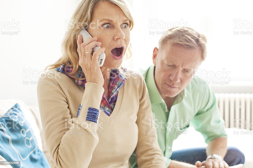 Very surprised woman talking on the phone stock photo