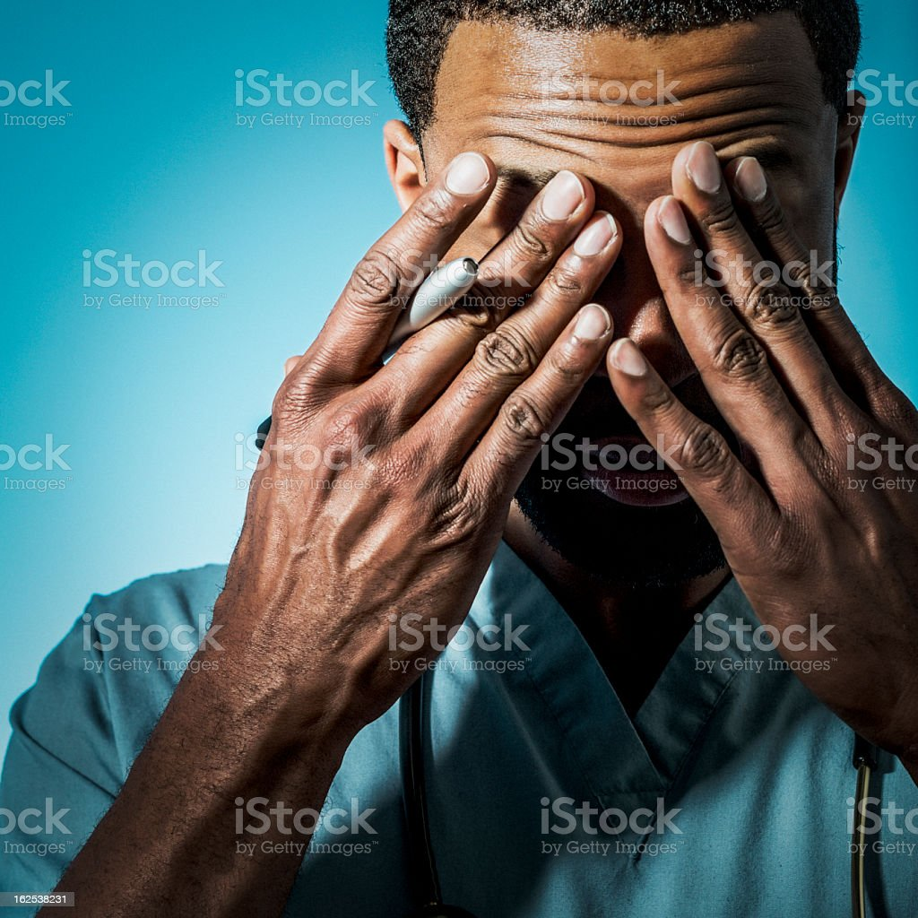 A very tired doctor holding his head stock photo