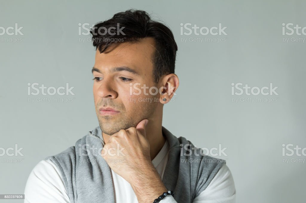 Very worried and sad man, hand on chin. Handsome brazilian wearing gray and white clothes, neutral. stock photo