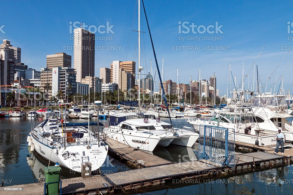 Vessels Moored at Yacht Mole Against City Skyline stock photo