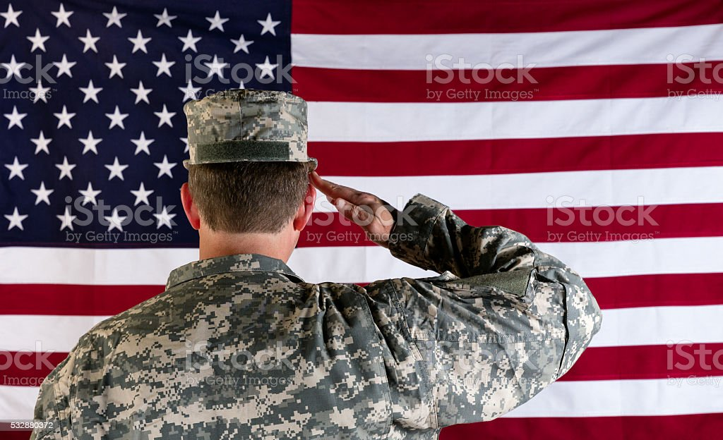 Veteran male solider saluting the flag of USA stock photo