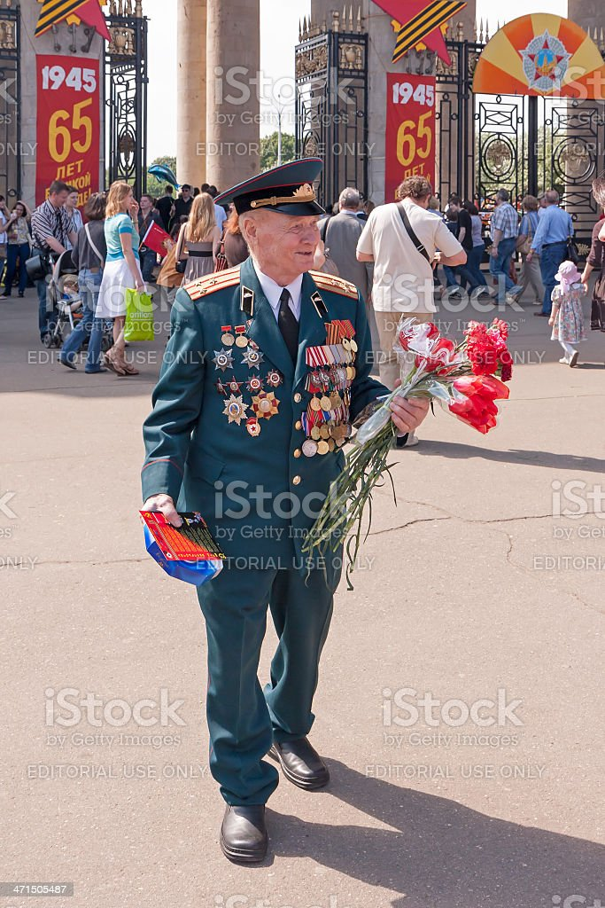 Veteran of WWII in uniform decorated with medals walks royalty-free stock photo