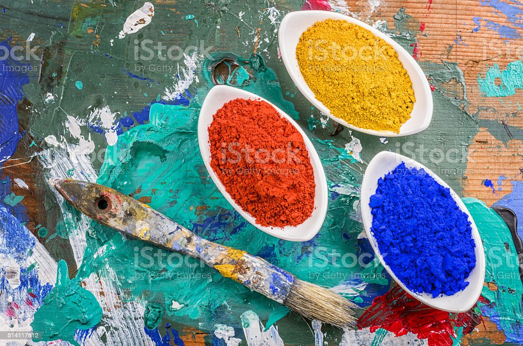Vibrant color pigments in porcelain bowls on a wooden palette stock photo